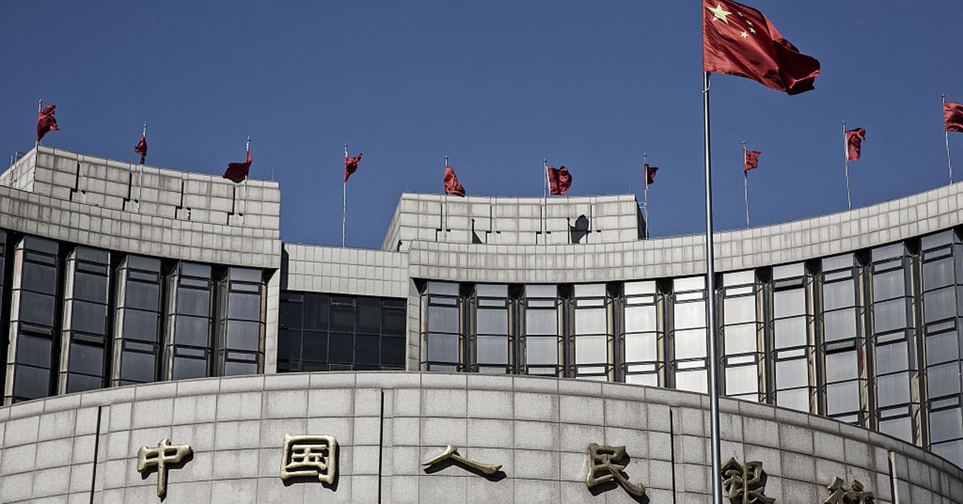 A Chinese national flag flies above the People's Bank of China (PBOC) headquarters in Beijing, China, on Monday, March 7, 2016.