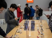 Customers look at mobile phones in a Xiaomi shop in Beijing on November 7, 2018. (Photo by Nicolas ASFOURI / AFP)        (Photo credit should read NICOLAS ASFOURI/AFP/Getty Images)